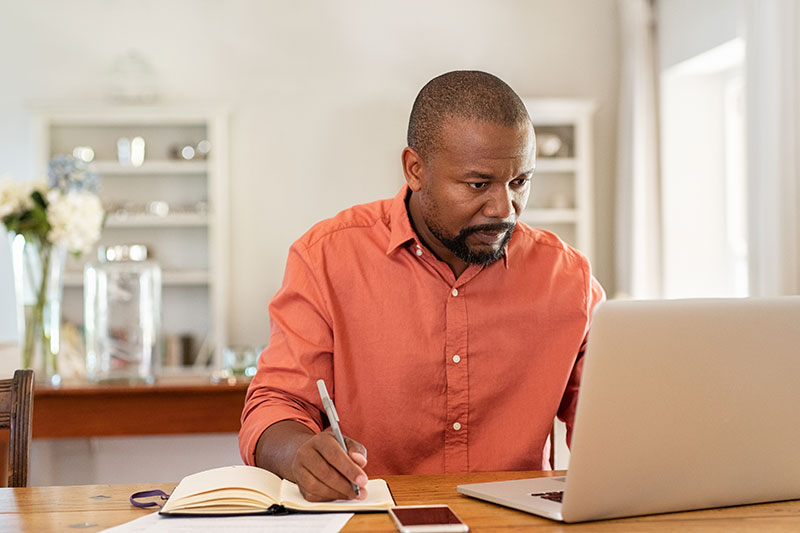 Mature man researching on his laptop